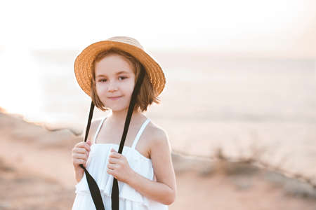 Smiling child girl 4-5 year old wearing straw hat with laces, swimsuit and denim shorts outdoors. Looking at camera. Summer time.