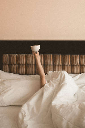 Girl wrapped in blanket with eye patches drinking coffee sitting in cozy bed try to wake up closeup. Good morning. Quarantine Social isolation.