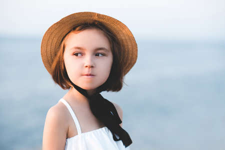 Smiling child girl 4-5 year old wearing straw hat with laces outdoors. Looking at camera. Summer time.