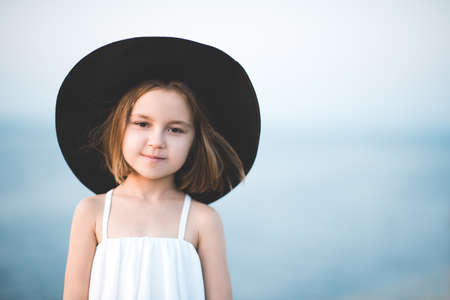 Smiling child girl 4-5 year old wearing big black hat and white top posing over blue sea background close up. Looking at camera. Summer travel season. 免版税图像