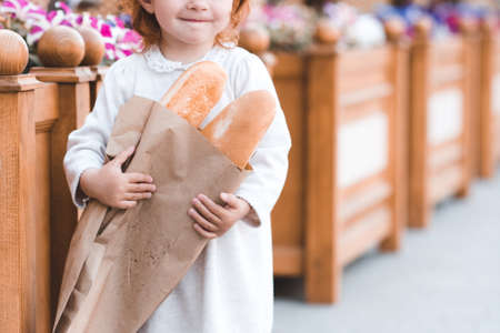 Little baby girl 3-4 year old holding fresh bread outdoors in cafe. Zdjęcie Seryjne