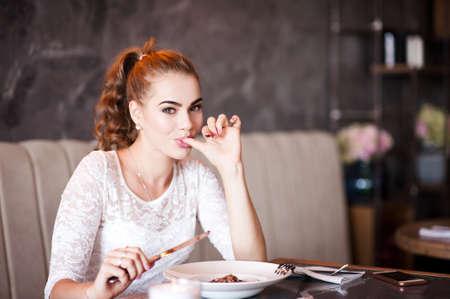 Beautiful blonde girl eating in cafe closeup. Looking at camera. 20s.
