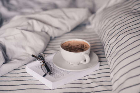 Cup of tasty fresh coffee staying on paper book with eyeglasses in bed closeup. Good morning. Breakfast Reklamní fotografie