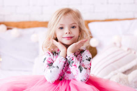 Happy kid girl 3-4 year old wearing princess dress in room. Good morning.