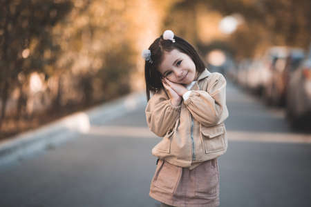 Pretty child girl 3-4 year old wearing stylish autumn clothes posing outdoors closeup. Looking at camera. Childhood.