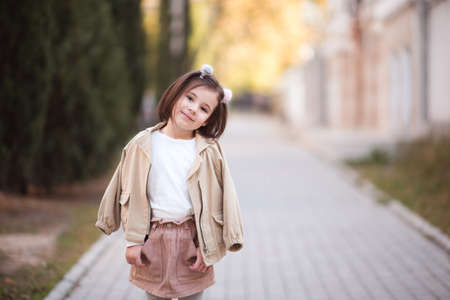 Pretty child girl 3-4 year old wearing stylish autumn clothes posing in street over city background closeup. Looking at camera. Childhood.