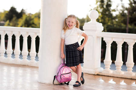 Laughing kid girl 5-6 year old wearing checkered skirt outdoors. Back to school. Pre schooler.