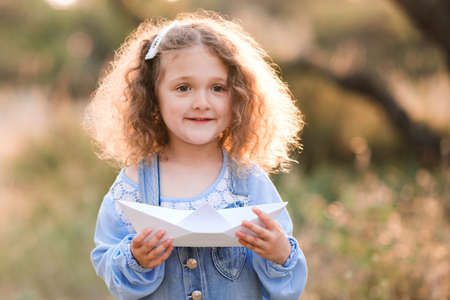 Cute kid girl 3-4 year old making paper origami ship outdoors. Childhood. Pre shcool. Stock Photo