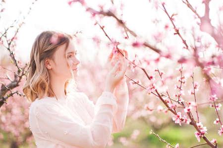 Girl walking in blooming peach orchard. Spring season. 20s.