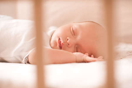 Cute baby sleeping in bed wearing knitted clothes closeup. Childhood. Reklamní fotografie