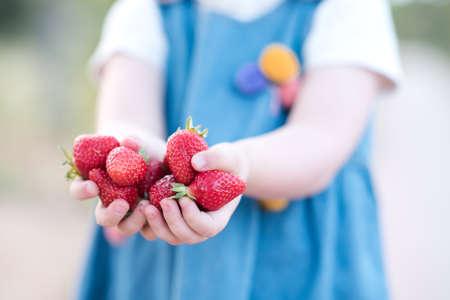Laughing baby girl pick up fresh strawberry outdoors closeup. Summer season. Childhood.