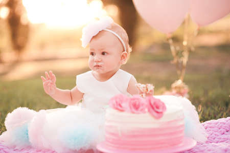 Baby girl 1 year old eating creamy birthday cake sitting on green grass with pink balloons in meadow outdoors closeup. Celebration. Childhood.