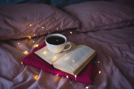 Open book with lights and tasty cup of tea in bed close up. Good morning. Selective focus. Winter holiday season. 写真素材