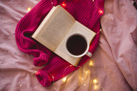 Cup of coffee with open book and knitted clothes over glowing lights in bed close up. Selective focus. Top view. 写真素材