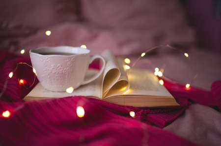 Cup of hot black tea staying on open book with heart shape folded pages and knitted pink sweater over glowing Christmas lights closeup in bed. Winter holiday season. Selective focus. 写真素材