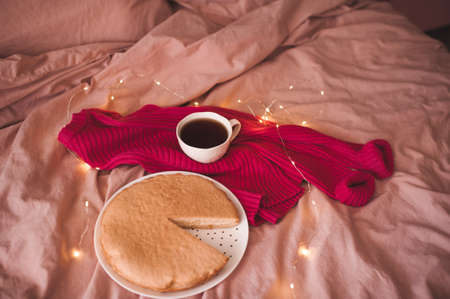 Cup of black tea with knitted cloth, tasty baked pie in bed with glowing Christmas lights. Selective focus. Winter holiday season. Good morning. 写真素材