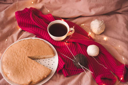 Cup of black tea with pink knitted cloth, tasty baked pie and yarning in bed with glowing Christmas lights. Selective focus. WInter holiday season. Good morning.
