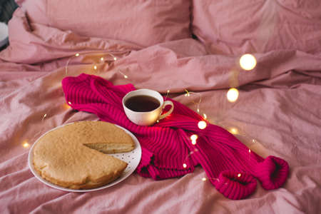 Cup of black tea with knitted cloth, tasty baked pie in bed with glowing Christmas lights. Selective focus. Winter holiday season. Cozy atmosphere.