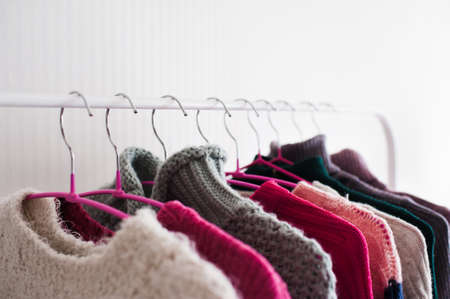 Colorful knitted clothes hang on hangers in shop closeup. Winter season. Selective focus. 写真素材