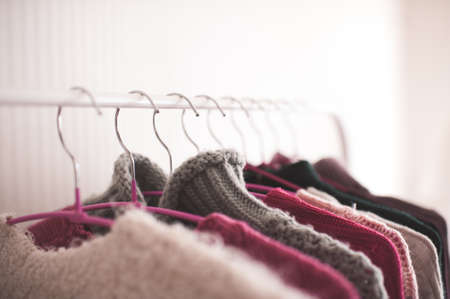 Clothes hangers with knitted sweaters on rack in shop close up. Selective focus. 写真素材