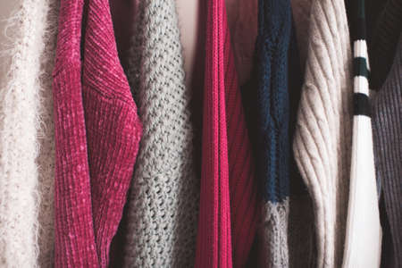 Knitted clothes hang on rack in shop closeup. Winter season. 写真素材