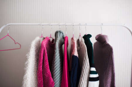 White rack with knitted sweaters in shop over wall closeup. Winter season. 写真素材