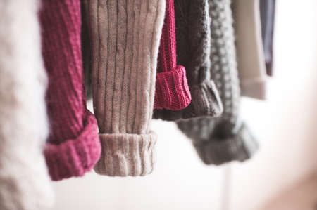 Knitted colorful clothes hang on rack indoors in shop. Season sale time. Selective focus. 写真素材