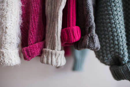 Knitted clothes with folded sleeves hang on hanger indoors closeup. Winter season. 写真素材