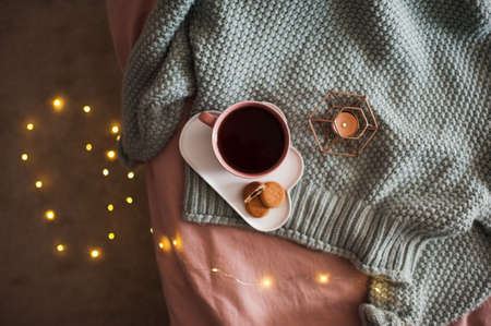 Cup of fresh coffee with tasty cookies with candle and glowing lights on knitted sweater in bed close up. Good morning. Breakfast time. Autumn season. Top view. 写真素材
