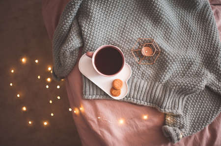 Mug of fresh black tea or coffee with tasty cookies with candle and glowing lights on knitted wool sweater in bed close up. Good morning. Breakfast time. Autumn season. Top view.