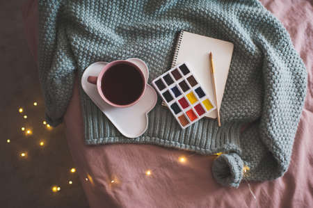 Cup of fresh coffee on plate with palette of paints, sketch book and knitted sweater over glowing Christmas lights at background in bed closeup. Winter season. Creative concept. Top view.