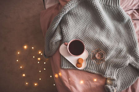Knitted sweater with fresh black tea or coffee with cookies and candle over Christmas glowing lights closeup. Good morning. Breakfast time. 写真素材