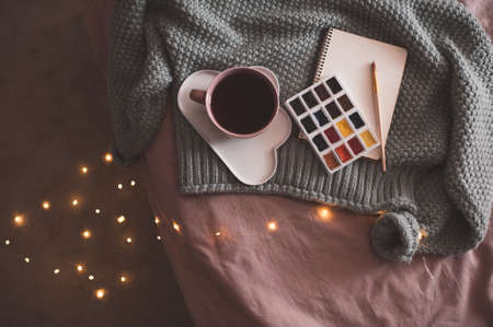 Cup of fresh coffee on plate with palette of paints, sketch book and knitted sweater over glowing Christmas lights at background in bed closeup. Winter season.