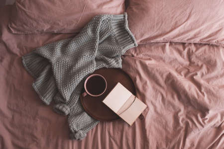 Fresh cup of coffee or black tea with open sketch book and knitted sweater in bed closeup. Good morning. Breakfast time.