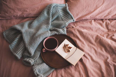 Cup of fresh coffee or tea with open sketch book with fallen autumn leaf on wooden tray and knitted sweater in bed close up. Good morning.