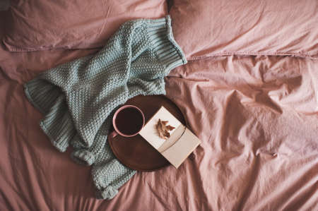 Cup of fresh coffee with open sketch book with fallen autumn leaf on wooden tray and knitted sweater in bed close up. Good morning.