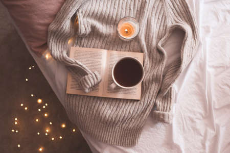 Cup of coffee or black tea staying on open book with burning candle and knitted gray sweater in bed over glowing Christmas lights close up. Winter holiday season. Top view.