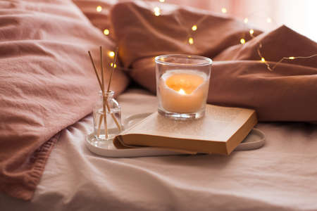 Burning candle with aroma sticks in bottle on tray with open book in bed over glowing Christmas lights close up. Cozy atmosphere at home. Good morning. Selective focus.
