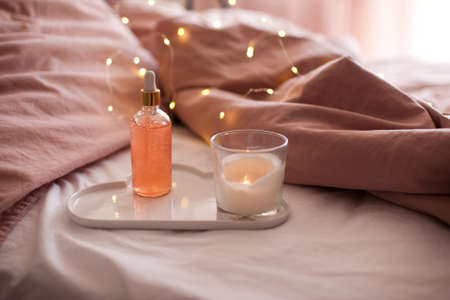 Moisturizing face serum in bottle with dropper staying on white ceramic tray with burning candle closeup in bed over glowing lights. Health care.