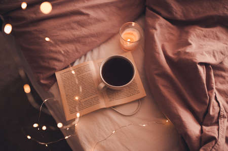 Cup of fresh hot coffee staying on open paper book with burning candle and glowing Christmas lights in bed closeup. Winter holiday season. Good morning. Selective focus. 写真素材