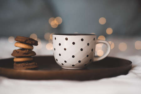 Cup of fresh hot tea with stack of chocolate cookies on wooden tray in bed close up. Good morning. Breakfast time. Focus on pastry.