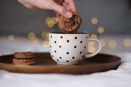 Chocolate cookie with hot milk in cup on wooden tray over glowing lights close up in bed. Good morning. Breakfast time. Selective focus. Winter holiday season.