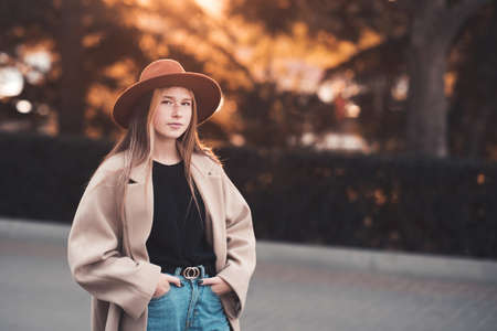 Blonde teen girl 13-14 year old wearing stylish coat and hat walking in city street over autumn nature background close up. Fall season. Teenagerhood. Looking at camera.