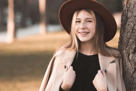 Smiling teenage girl 13-14 year old wearing stylish hat and beige winter coat posing over autumn background close up. Teenagerhood.