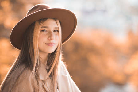 Smiling teen girl 12-13 year old wearing stylish hat and beige jacket over yellow nature close up. Teenagerhood. Autumn season. Looking at camera.