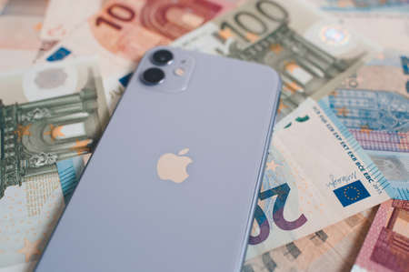 Moscow / Russia - October 10, 2020: new iphone in purple shade on different money banknotes close up. Editoriali