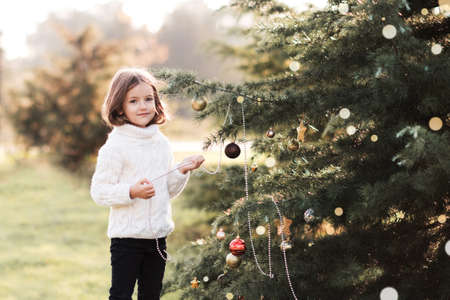 Pretty baby girl 3-4 year old decorate Christmas tree wearing knitted white sweater outdoors close up. Looking at camera. New Year. Childhood. Archivio Fotografico