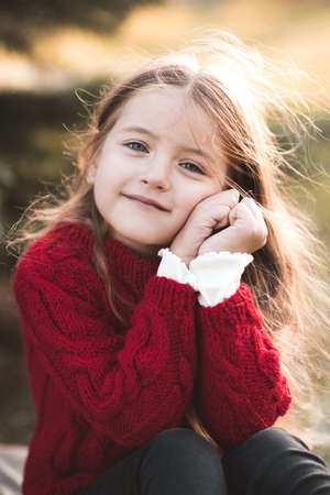 Smiling baby girl 3-4 year old wearing knitted red sweater posing over nature background close up. Looking at camera. Childhood. Autumn season. Archivio Fotografico