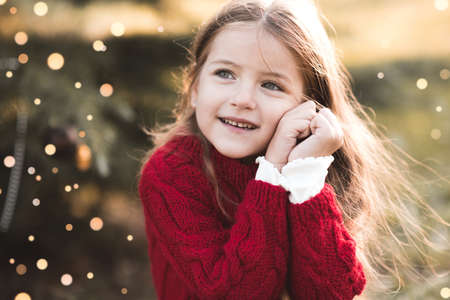 Laughing happy child girl 4-5 year old with blonde long hair wearing knitted red sweater over Christmas glowing lights at background close up. Childhood. New Year. Healthy lifestyle. Archivio Fotografico