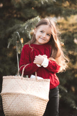 Smiling kid girl 3-4 year old wearing red knitted sweater holding straw basket over nature background outdoors close up. Childhood. Looking at camera.